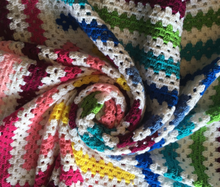 A fun view of the bold colors of the free crochet pattern Log Cabin Twist by CoffeeandCrochetGoals
